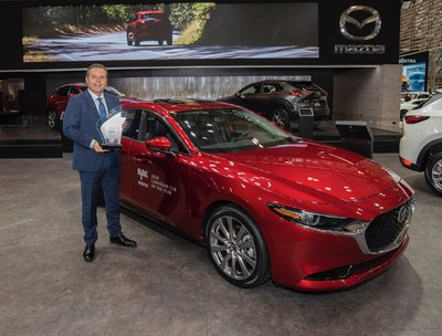 David Klan, President  CEO, Mazda Canada holding the trophy for the 2020 AJAC Canadian Car of the Year in front of the award-winning Mazda3 (CNW Group/Mazda Canada Inc.)